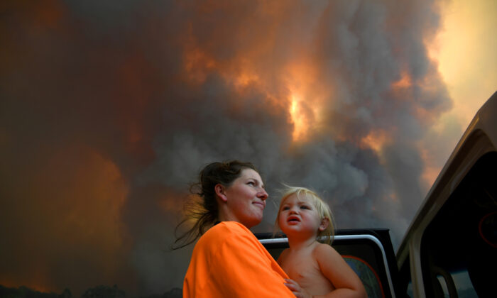 Sharnie Moren and her 18-month-old daughter Charlotte look on as thick smoke rises from bushfires near Nana Glen, near Coffs Harbour, Australia, on Nov. 12, 2019. (Dan Peled/AAP via Reuters)