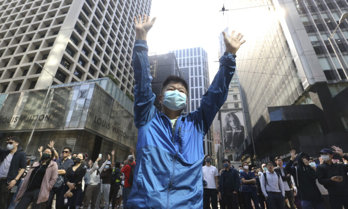 A demonstrator raises his hands during a protest in the financial district in Hong Kong on Nov. 15, 2019. Protesters who have barricaded themselves in a Hong Kong university partially cleared a road they were blocking and demanded that the government commit to holding local elections on Nov. 24. (Achmad Ibrahim/AP)