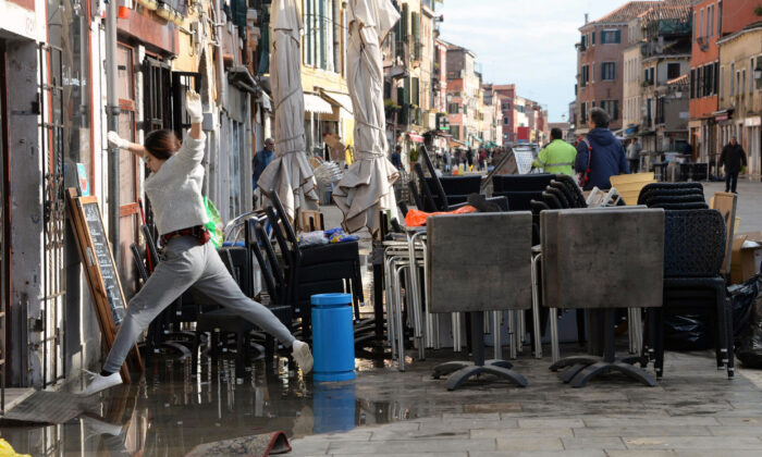 A woman jumps over a puddle during cleaning following a flooding in Venice, Italy, Thursday, Nov. 14, 2019. (Andrea Merola/ANSA via AP)
