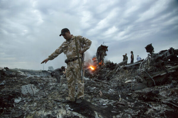 People walk amongst the debris at the crash site of Malaysia Airlines Flight 17