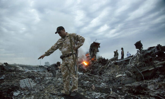 People walk amongst the debris at the crash site of Malaysia Airlines Flight 17 (MH17) passenger plane near the village of Grabovo, Ukraine, on July 17, 2014. (Dmitry Lovetsky/ AP Photo)