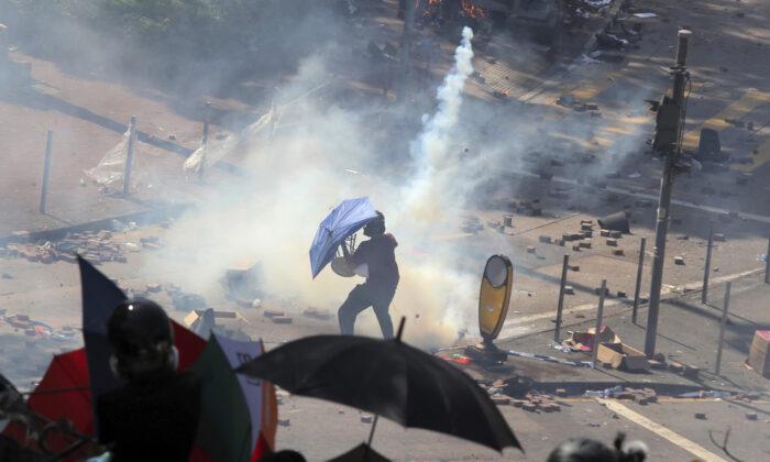 A protestor reacts as police fire tear gas at Hong Kong Polytechnic University in Hong Kong, on Nov. 17, 2019. (AP Photo/Kin Cheung)