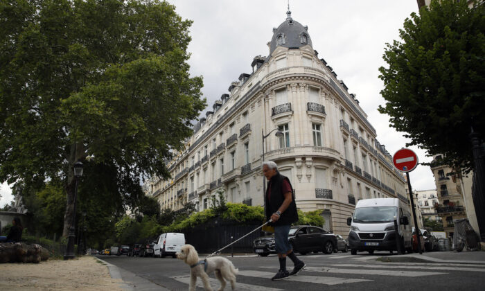 In this Aug.13, 2019 file photo, a man walks his dog next to an apartment building owned by Jeffrey Epstein in the 16th district in Paris on Aug. 13, 2019. (AP Photo/Francois Mori, File)