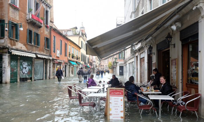 People sit at a cafe in a flooded street during a period of seasonal high water in Venice, Italy, on Nov. 17, 2019. (Manuel Silvestri/Reuters)