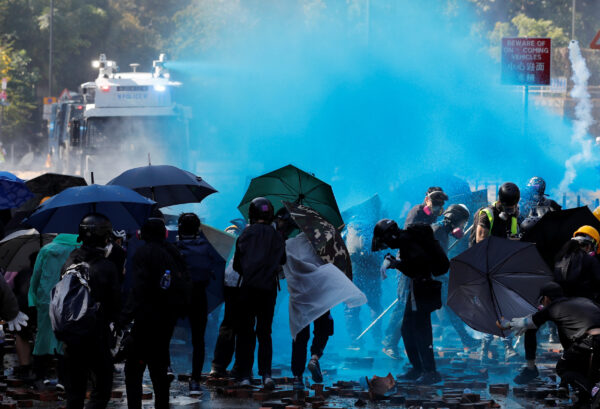 Protesters are sprayed with blue liquid from water cannon during clashes with police outside Hong Kong Polytechnic University