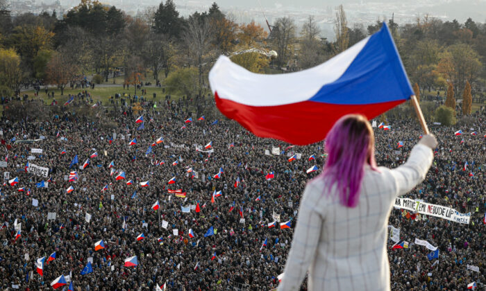 A woman waves a Czech flag from a roof as people take part in a large anti-government protest in Prague, Czech Republic on Nov. 16, 2019. (Petr David Josek/AP)