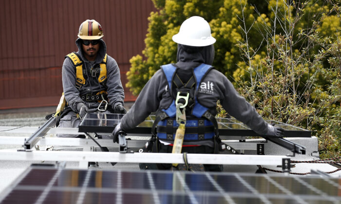 Workers install solar panels on the roof of a home on May 9, 2018 in San Francisco, Calif., on May 9, 2018. (Justin Sullivan/Getty Images)