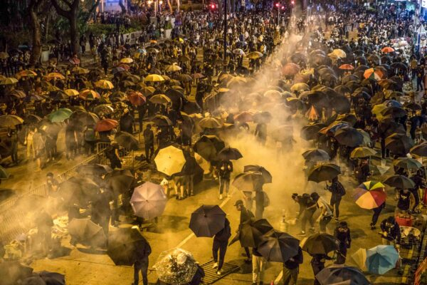 Protesters react as police fire tear gas while they attempt to march towards Hong Kong Polytechnic University in Hung Hom district of Hong Kong.