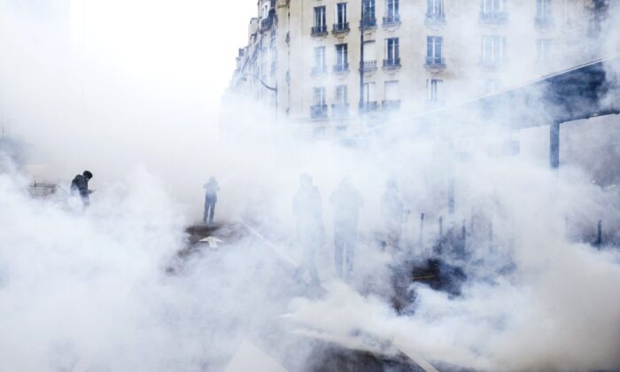 Tear gas envelopes protesters during a yellow vest demonstration marking the first anniversary in Paris, on Nov. 16, 2019. (Kamil Zihnioglu/AP Photo)