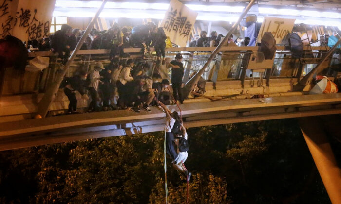 Pro-democracy protesters trapped inside Hong Kong Polytechnic University abseil onto a highway and escape before being forced to surrender during a police siege of the campus in Hong Kong, China on Nov. 18, 2019. (HK01/Handout via Reuters)