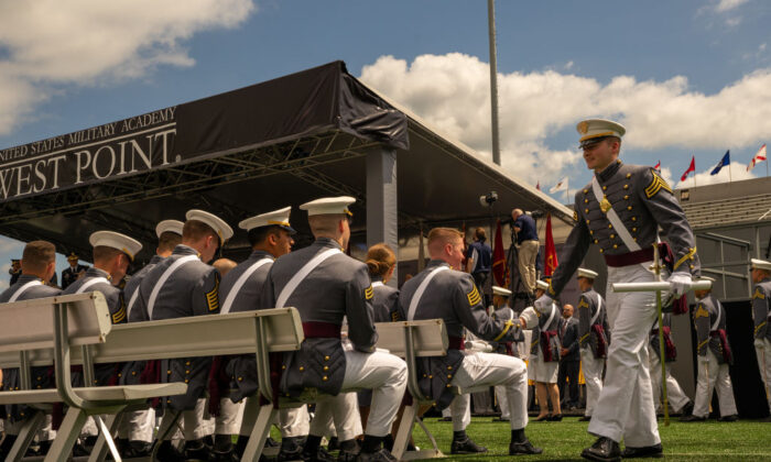 A graduating cadet walks with his diploma as he is congratulated by a classmate during graduation ceremony of the U.S. Military Academy Class of 2019 graduation ceremony at Michie Stadium in West Point, New York, on May 25, 2019. (David Dee Delgado/Getty Images)