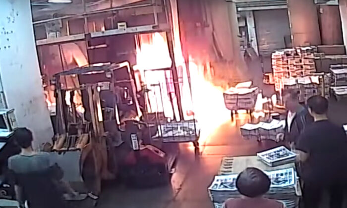 Staff at the print shop that prints the Hong Kong edition of The Epoch Times react to a fire started by four masked men on Nov. 19, 2019.