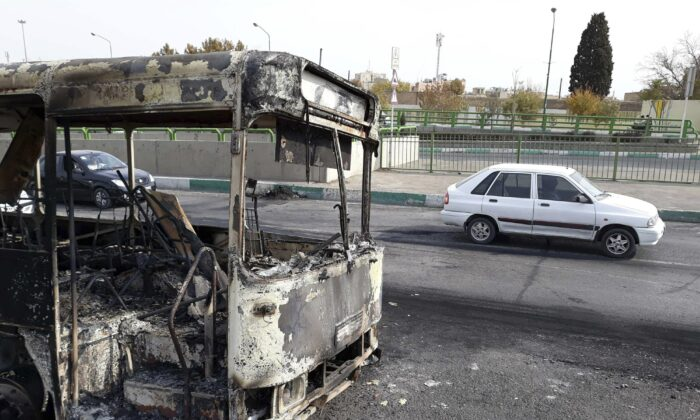 A scorched public bus remained on the street after protests that followed authorities' decision to raise gasoline prices, in Tehran, Iran, on Nov. 17, 2019. (Morteza Zangane/ISNA via AP)
