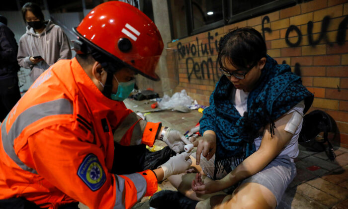 A protester receives medical attention inside the Hong Kong Polytechnic University campus during protests in Hong Kong, China on Nov. 19, 2019. (Adnan Abidi/Reuters)