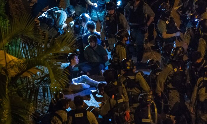 Police detain protesters and students after they tried to flee outside the Hong Kong Polytechnic University campus in the Hung Hom district in Hong Kong, on Nov. 19, 2019. (Billy H.C. Kwok/Getty Images)