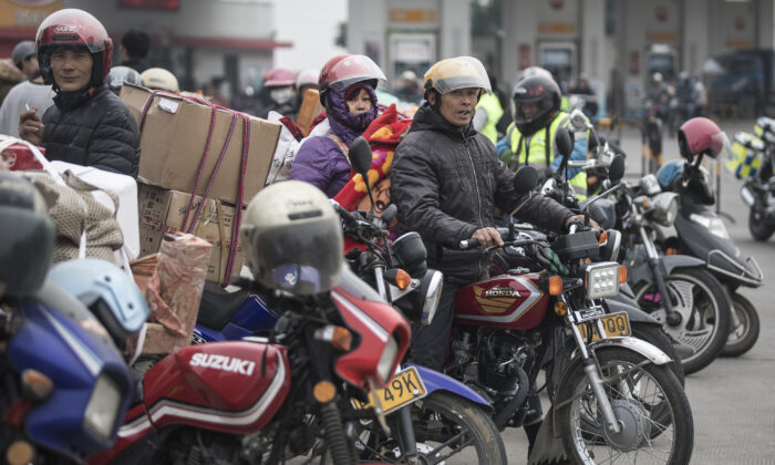 Chinese migrant workers rest at gas stations after riding motorcycles in Zhaoqing, Guangdong Province, China on Jan. 25, 2019. They are going back home together ahead of the Chinese New Year. (Wang He/Getty Images)