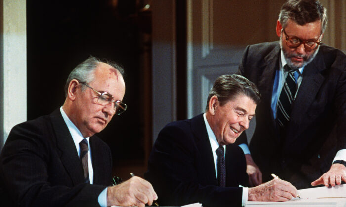 Soviet leader Mikhail Gorbachev (L) and US President Ronald Reagan sign at the Washington summit a treaty eliminating US and Soviet intermediate-range and shorter-range nuke missiles, on Dec. 8, 1987.  (-/AFP via Getty Images)