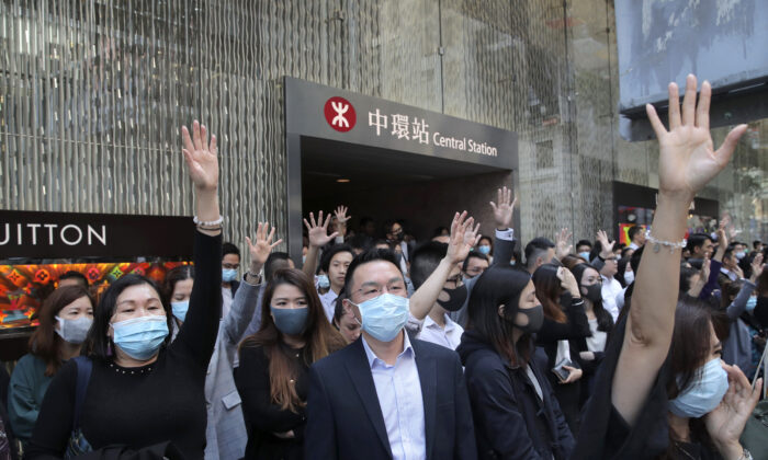 Protesters hold up their hands to symbolize pro-democracy demonstrators' five demands during a demonstration in the financial district in Hong Kong, Wednesday, Nov. 20, 2019. (AP Photo/Kin Cheung)