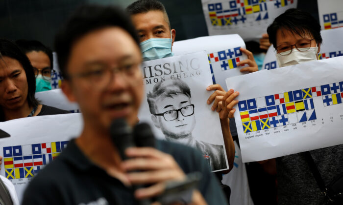 A demonstrator holds a poster of Simon Cheng, a staff member at the consulate who went missing on Aug. 9 after visiting the neighboring mainland city of Shenzhen, as he and others shout slogans during a protest outside the British Consulate-general office in Hong Kong, China, on Aug. 21, 2019. (Willy Kurniawan/Reuters)