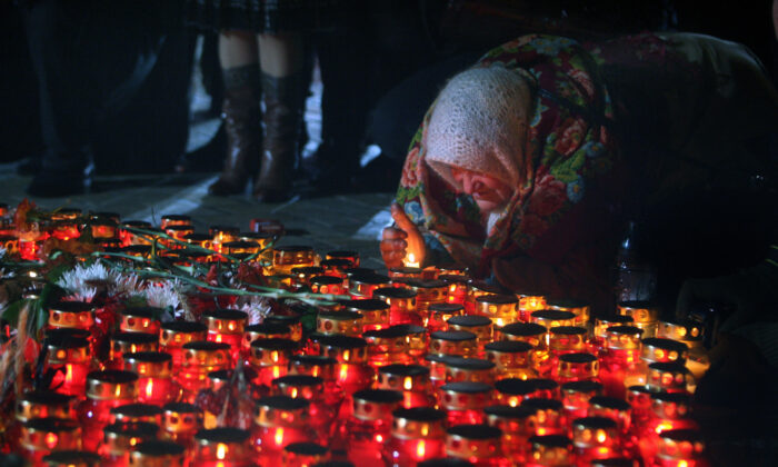 A woman kneels to light a candle during a mass memorial meeting at the Holodomor victims monument in Kiev, 24 Nov. 2007. (Sergei Supinsky/AFP via Getty Images)