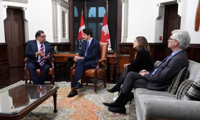 Deputy Prime Minister Chrystia Freeland and Jim Carr look on as Prime Minister Justin Trudeau speaks with Calgary mayor NaheedNenshiin his office on Parliament Hill in Ottawa on Nov. 21, 2019. (The Canadian Press/Adrian Wyld)