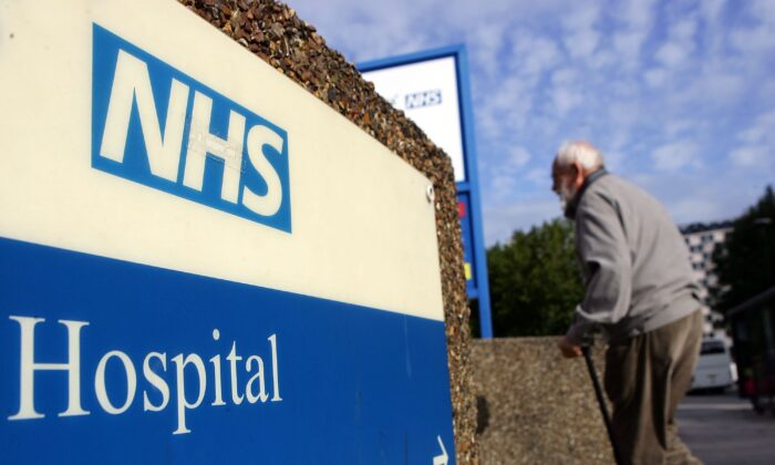 An elderly gentleman walks past a hospital sign in London on Sept 26, 2007. (Cate Gillon/Getty Images)