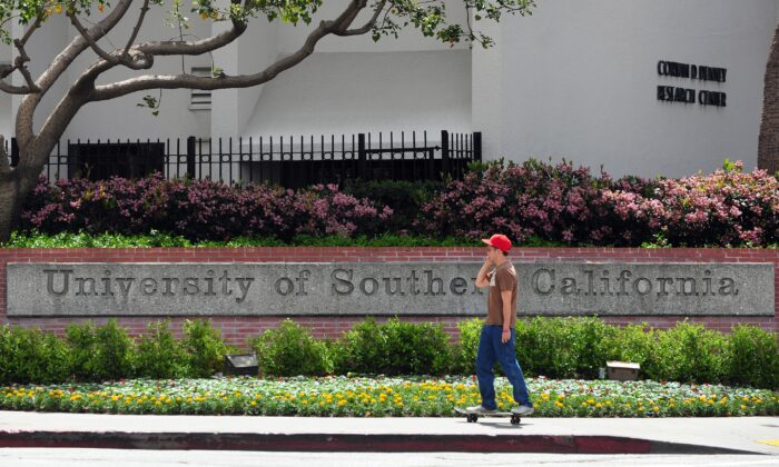 A student rides his skateboard past an entrance to the University of Southern California (USC) campus in Los Angeles, U.S. on April 11, 2012. (Frederic J. Brown/AFP via Getty Images)