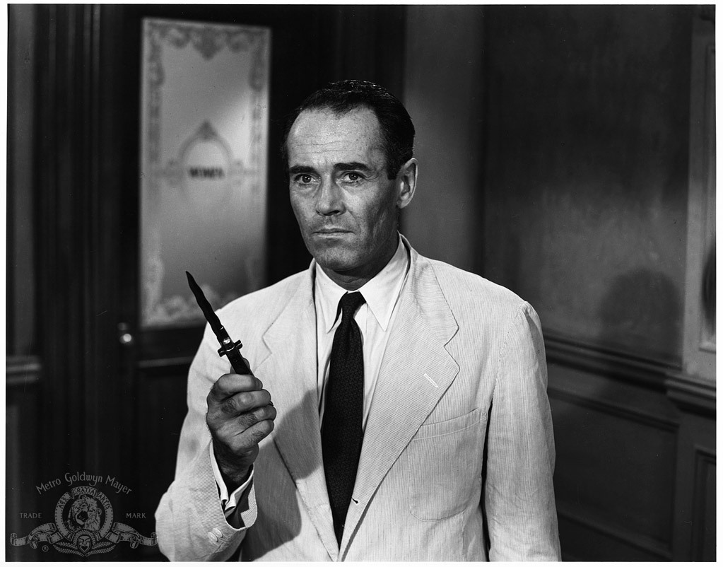 man in white suit holding switchblade