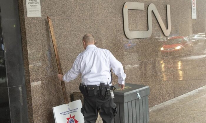 """A security guard removes a picket sign in front of theCNheadquarters as Canadian National Railway workers begin a nationwide strike on Nov. 19, 2019 in Montreal. The Teamsters union that went on strike this week claiming Quebec's propane shortage """"appears to be largely manufactured"""" by Canadian National Railway Co. (The Canadian Press/Ryan Remiorz)"""