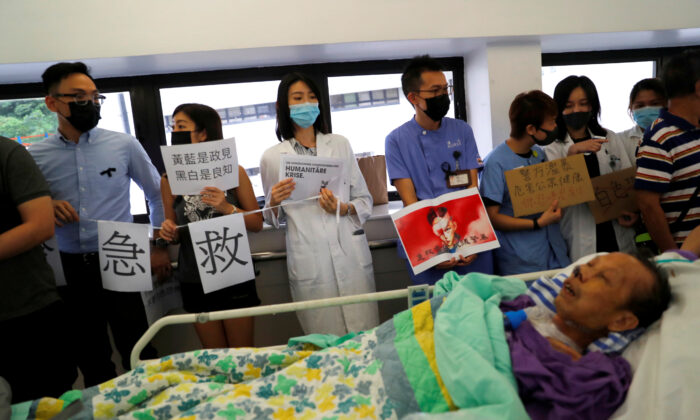 A patient is wheeled past as healthcare staff hold posters and participate in a human chain to protest against what they say is police brutality during the anti-extradition bill protests, at Queen Mary Hospital, in Hong Kong, China, on Sept. 2, 2019. (Anushree Fadnavis/Reuters)