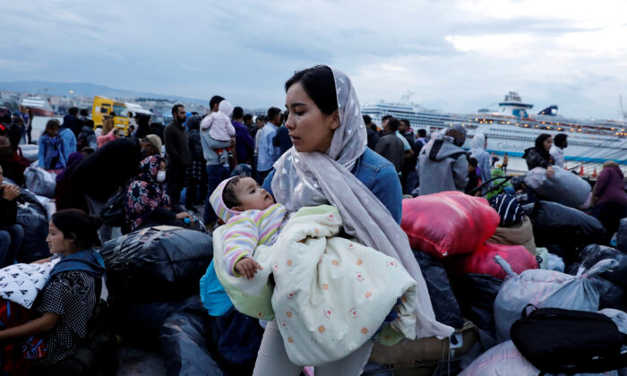 A woman holds her baby as refugees and migrants arrive on a passenger ferry from the island of Lesbos at the port of Piraeus, Greece, on Oct. 7, 2019. (Giorgos Moutafis/Reuters/File Photo)