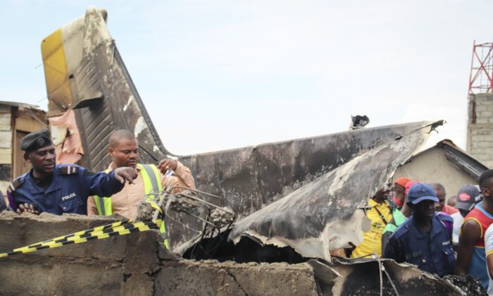 Rescuers and onlookers gather amidst the debris of an aircraft operated by private carrier Busy Bee which crashed in Goma, Congo on Nov. 24, 2019. (Justin Kabumba/AP Photo)