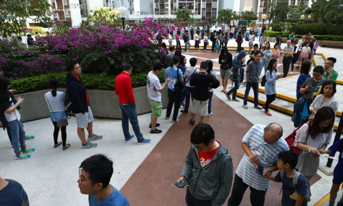 Voters queue to vote at a polling station during district council local elections on Hong Kong Island, China on Nov. 24, 2019. (Athit Perawongmetha/Reuters)