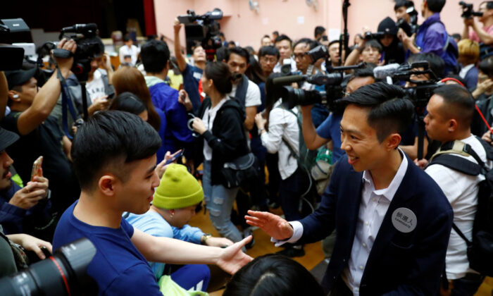 Local candidate Kelvin Lam celebrates with supporters after it was announced he won the local council elections in his district, at a polling station in the South Horizons West district in Hong Kong, on Nov. 25, 2019. (Thomas Peter/Reuters)