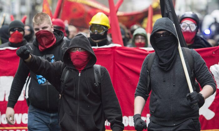 Masked demonstrators take part in an anti-capitalist protest on May Day in Montreal on May 1, 2016. Partially seen on the right of the red banner is the communist hammer and sickle symbol. (The Canadian Press/Graham Hughes)