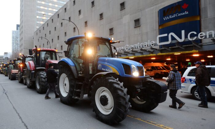 Farmers park their tractors in protest outside the Canadian National Railway headquarters in Montreal on Nov. 22, 2019. (The Canadian Press/Ryan Remiorz)