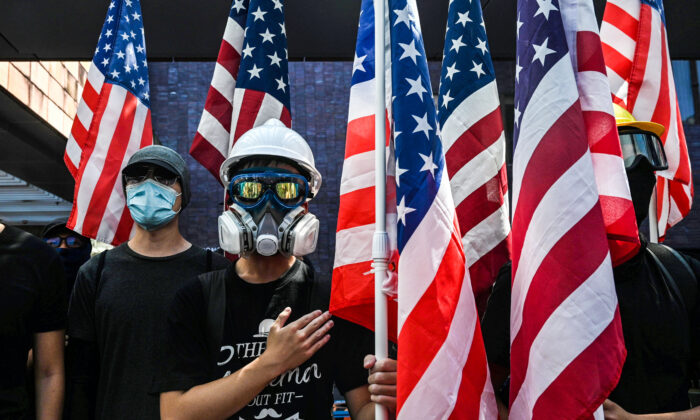 Students hold the US flag and sing the Star-Spangled Banner at Hong Kong University (HKU) at Hong Kong on September 20, 2019, as they rally for the US Congress to pass the Hong Kong Human Rights and Democracy Act. (Photo by Anthony WALLACE / AFP)        (Photo credit should read ANTHONY WALLACE/AFP via Getty Images)