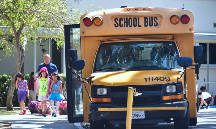 Children walk past a school bus in Monterey Park, Calif., on April 28, 2017.  (FREDERIC J. BROWN/AFP via Getty Images)