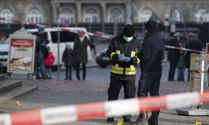 Police officers stand behind a caution tape at the Schinkelwache building in Dresden on Nov. 25, 2019. (Sebastian Kahnert/dpa via AP)