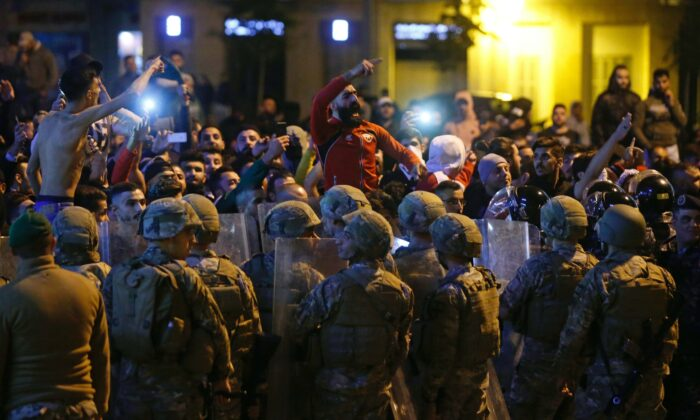 Lebanese army soldiers and riot police are deployed after clashes broke out between anti-government demonstrators and supporters of the Shi'ite movements Hezbollah and Amal in Beirut, Lebanon, on Nov, 25, 2019. (Mohamed Azakir/Reuters)