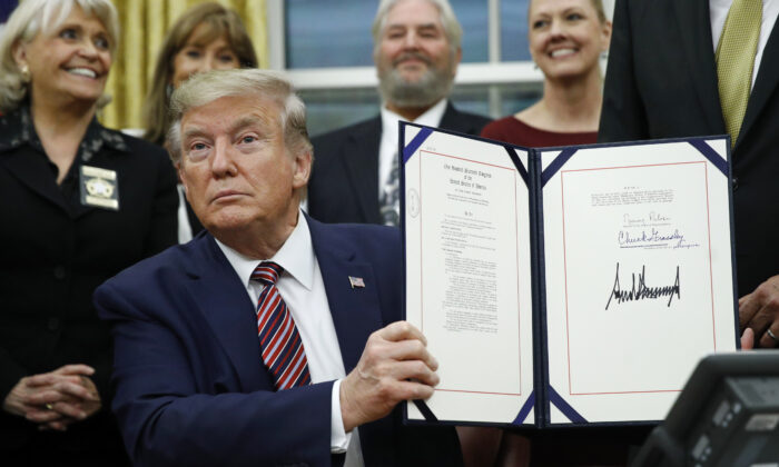 President Donald Trump displays the Preventing Animal Cruelty and Torture Act after signing it during a ceremony in the Oval Office of the White House, on Nov. 25, 2019. (Patrick Semansky/AP Photo)