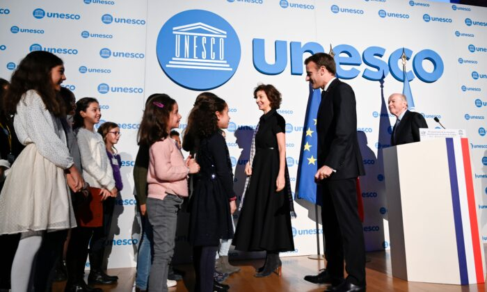UNESCO Director-General Audrey Azoulay (3rd R), French President Emmanuel Macron (2nd R) and French Ombudsman Jacques Toubon (R) welcome children during the 30th anniversary of the Convention on the Rights of the Child at the UNESCO in Paris on Nov. 20, 2019. (Photo by Eric Feferberg / POOL / AFP)