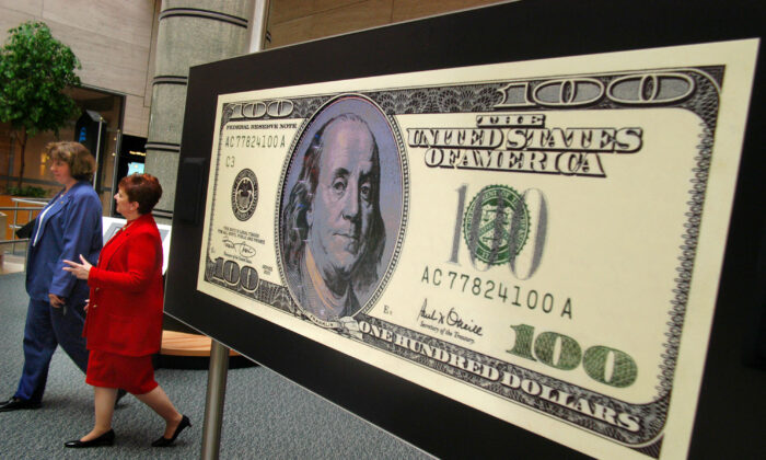 "Two unidentified women walk past a video $100 bill during a tour of the ""Money in Motion"" exhibit at the Philadelphia Federal Reserve Bank in Philadelphia, Penn., on July 2, 2003. (William Thomas Cain/Getty Images)"