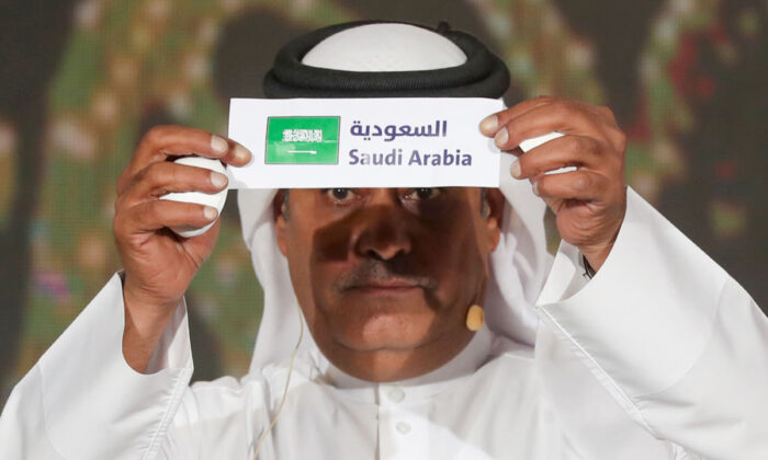 Hamed al-Hajri, a member of the Qatar Football Association, holds up the name of Saudi Arabia during the group draw for the 24th Arabian Gulf Cup in the capital Doha on Nov. 14, 2019. (Karim Jaafar/AFP via Getty Images)