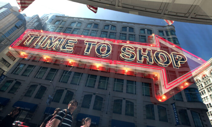 """Pedestrians walk by a sign at an Old Navy store in San Francisco, Calif., on Aug. 25, 2009. The New York-based Conference Board reported that while its Consumer Confidence index dropped in November, it remains high """"and should support solid holiday spending."""" (Justin Sullivan/Getty Images)"""