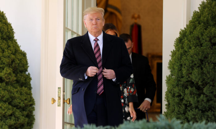 President Donald Trump steps out of the Oval Office before posing for photographs with Conan, the U.S. military K9 that assisted in the raid that killed ISIS leader Abu Bakr al-Baghdadi, on the Rose Garden colonnade at the White House in Washington on Nov. 25, 2019. (Chip Somodevilla/Getty Images)