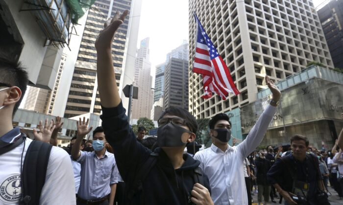 Demonstrators raise their hands during a protest in the financial district in Hong Kong on Nov. 15, 2019. (Achmad Ibrahim/AP)