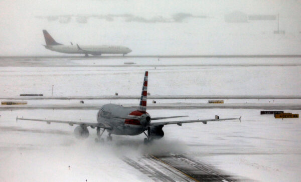 An American Airlines jet taxis down a snow-covered runway after a snowstorm at Denver International Airport