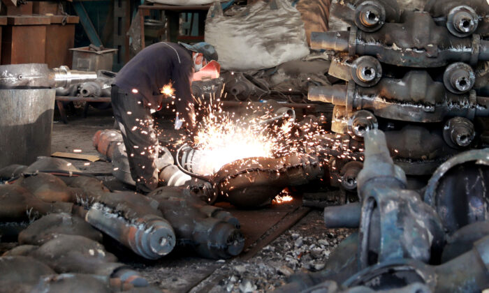 A worker welds automobile parts at a workshop manufacturing automobile accessories in Huaibei, Anhui Province, China on June 28, 2019. (Reuters)