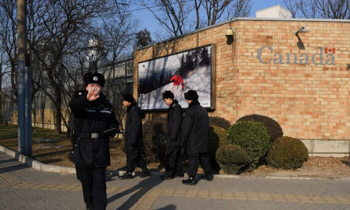 A Chinese policeman tries to block the photographer at the Canadian Embassy in Beijing on Dec. 14, 2018. (Greg Baker/AFP via Getty Images)